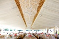 Wedding tent with a ruffled center of white and gold, crystal chandeliers, and glass globes