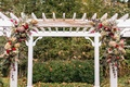 white arch over altar with wine-colored floral vines in red purple pink and green