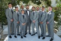 groom in grey suit with groomsmen in similar light grey suits black shoes and ties white pockets