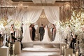 Bride and groom under white drapery chuppah at indoor Chicago wedding with rustic flower arrangement