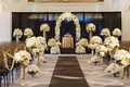 indoor wedding with black, gold, and ivory, multiple flower arrangements