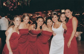 Bride with six bridesmaids wearing red silk bridesmaid dresses