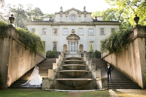 bride and groom on separate stairwells in front of stately southern mansion