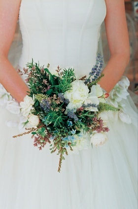 Bride holds natural loose wildflower bouquet