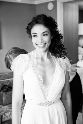 Black and white photo of bride in a Jenny Packham dress with lace sleeves & details at neckline