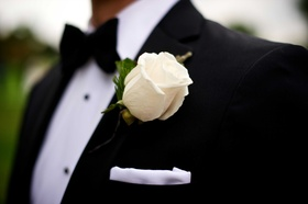 Groom in black tuxedo, bow tie & white pocket square, rose boutonniere