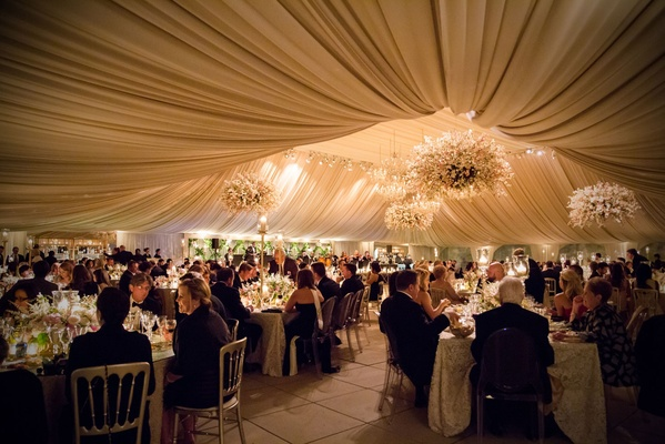 Guests enjoying dinner at wedding reception in heavily draped ballroom with flower chandeliers