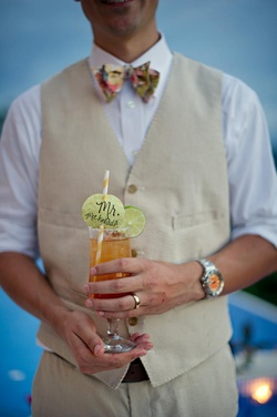 Groom holding michelada cocktail with special straw
