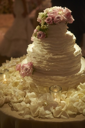 Four layer cake with fresh pink roses and flowers