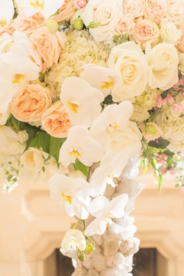 Wedding reception centerpiece of white orchids, hydrangeas, tulips, roses, peach garden roses