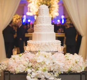 White wedding cake with rosettes covering one layer, lace design on others, surrounded by flowers