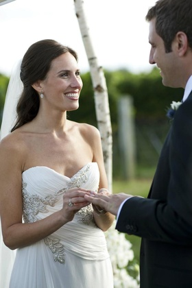 Bride smiling and putting wedding band on husband