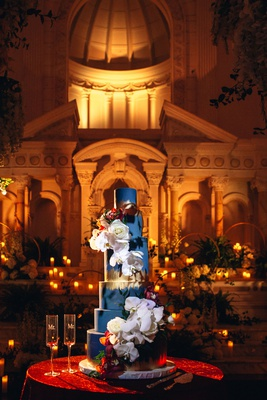 six-tier blue cake with gold foil and white orchids and roses