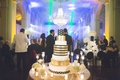 New Year's Eve wedding cake with gold stripes and polka dots under chandelier NYE