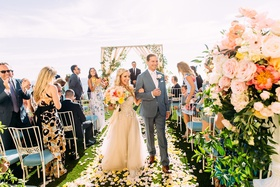 bride in custom trish peng wedding dress groom walking up aisle yellow flower petals blue chairs