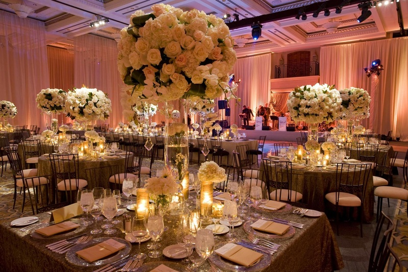 Wedding reception in a ballroom draped with pink fabric and light arrangements on tables