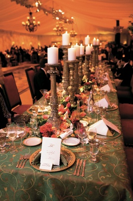 Wedding reception table with green embroidered tablecloth and white candles on golden candleholders
