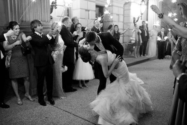Black and white photo of bride in mermaid dress strapless kisses groom during sparkler exit