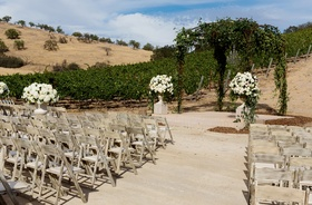 Wood chairs and white flowers at winery wedding