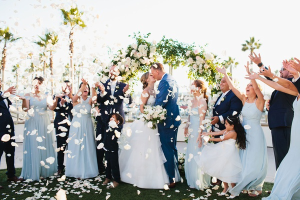bride and groom kiss bridesmaids and groomsmen toss rose petals ocean view ceremony palm trees