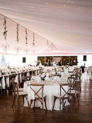 Wedding reception wood flooring white tent chandeliers x back wood chairs white linens flowers