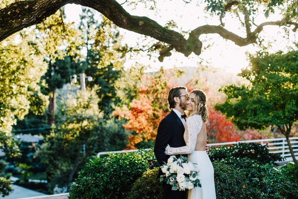bride in backless dress with lace sleeves, groom in tuxedo, fall foliage