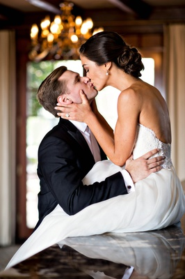 bride in reem acra, groom in white tie tuxedo, bride sits on counter to kiss groom