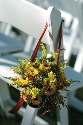 Autumn flowers and foliage hanging from white ceremony chair