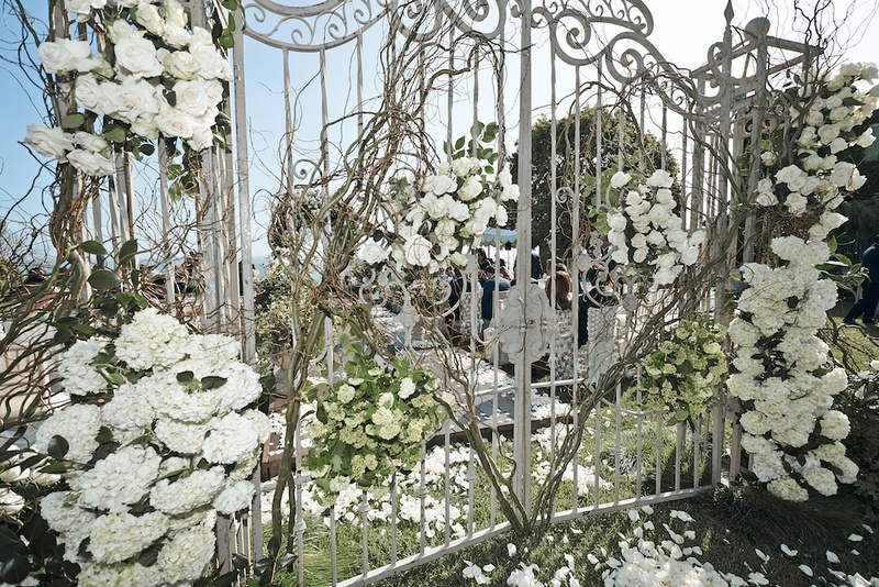White wrought-iron gate adorned with flowers