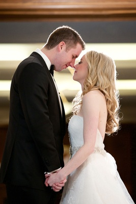 Bride in Vera Wang strapless wedding dress long blonde hair eskimo kiss with groom in tuxedo Chicago