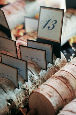Small log holds place cards for a wedding reception