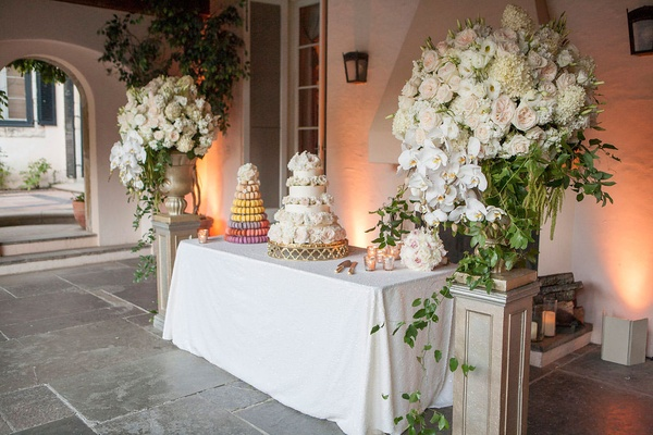 dessert table tower of macarons white cake flowers flanked by tall white green floral arrangements