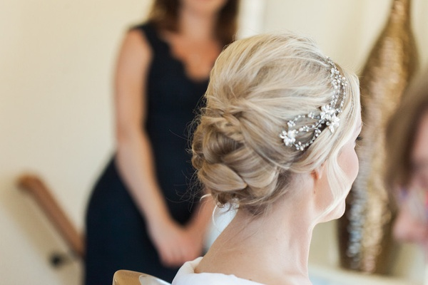 Bride's updo hairstyle with sparkling headband headpiece with flowers