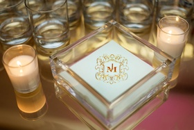 Wedding reception beverage napkin with monogram surrounded by candles