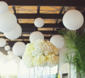Wedding reception table with tall centerpiece of white hydrangeas and crystal strands
