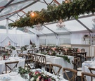 wedding reception tent clear top wood vineyard chairs greenery chandelier low centerpieces