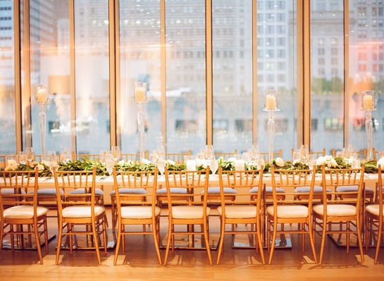 long table with gold chiavari chairs, moss and white rose centerpieces with elevated candles
