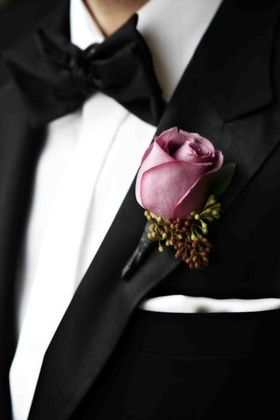 Groom wearing lavender pink rose on tuxedo lapel
