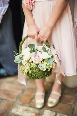 Flower girl in light pink dress and gold ballet flats with bows holding green moss basket pink rose