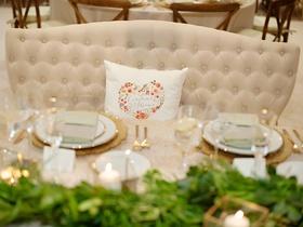 Wedding reception decor rustic wedding green garland gold place setting heart pillow on settee
