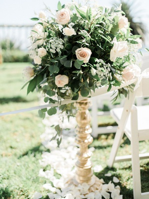 wedding ceremony gold stand greenery leaves pink white rose flower petals on grass