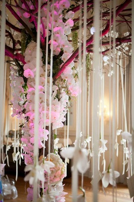 Wedding place card table decorated with a tree decorated with white orchids and ribbons