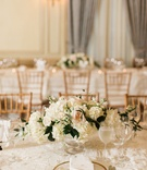 Wedding reception neutral classic table decor with white blush flowers and gold chairs drapery