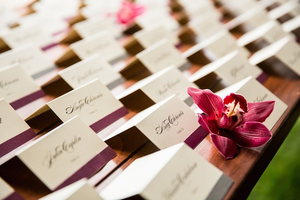 White escort cards with black script and purple ribbon at bottom