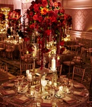 red rose centerpieces with cascading crystals, pillar candles, gold linens and gold chairs