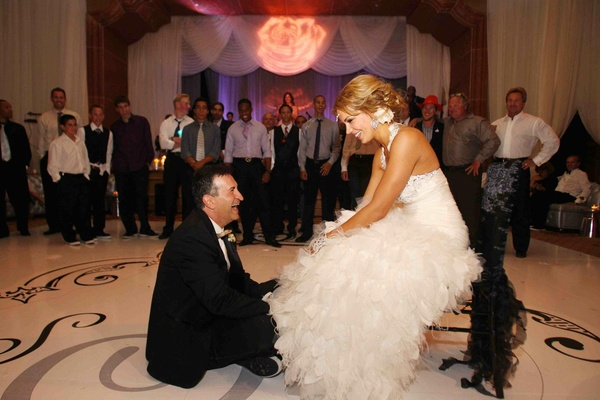 Groom on floor and bride sitting on chair