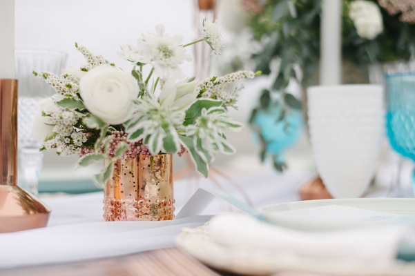 small rose gold stand with white and green floral arrangement on blue and white tablescape