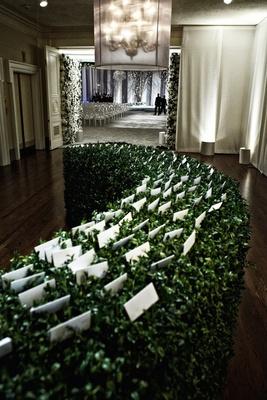 Wedding escort cards on green leaf hedge in ballroom