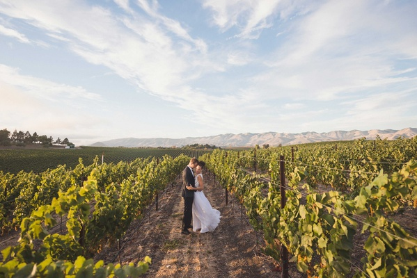 Bride in Mira Zwillinger wedding dress from Carine's Bridal Atelier in vineyard winery SLO
