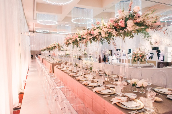 Long reception table with tall centerpiece design pink flowers, leaves, white flowers, glass orbs